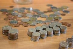 Moneta di baht tailandese sul pavimento di legno Immagine Stock