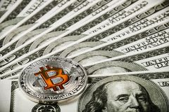 Moneta di Bitcoin su fondo delle banconote dei dollari Immagine Stock