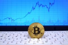 Moneta di bitcoin sulla tastiera bianca con il grafico di tasso di cambio sulle sedere Immagine Stock Libera da Diritti