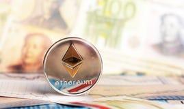 Moneta di Ethereum contro delle banconote differenti fotografia stock