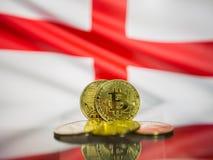 Moneta di oro di Bitcoin e bandiera defocused del fondo dell'Inghilterra Concetto virtuale di cryptocurrency fotografie stock libere da diritti