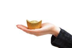 Moneta di oro che tiene sopra una mano con i manicotti neri fotografia stock