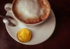 Moneta di oro del bitcoin e del Capuccino sulla tavola nella vista superiore del caffè Fotografie Stock