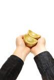 Moneta di oro due che tiene sopra una mano con i manicotti neri fotografia stock
