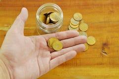 Moneta di oro sulla mano umana per risparmiare Fotografia Stock Libera da Diritti