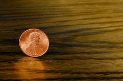 Moneta di rame del centesimo su fondo di legno Fotografie Stock