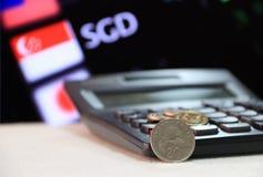 Moneta di Singapore da venti centesimi sullo SGD inverso con il calcolatore nero ed il bordo digitale del fondo dei soldi di camb fotografie stock