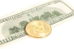 Moneta dorata del bitcoin e cento banconote del dollaro Fotografie Stock