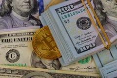 Moneta dorata di Bitcoin dei soldi virtuali di cryptocurrency sulla fattura di dollaro americano degli Stati Uniti fotografia stock libera da diritti