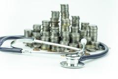 Moneta e stetoscopio tailandesi del bagno su fondo bianco Fotografia Stock Libera da Diritti