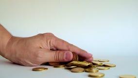 Moneta falsa della mano sulla pila di moneta di oro su fondo bianco, 4k, UHD stock footage