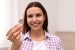 Moneta felice della tenuta della giovane donna a casa fotografie stock libere da diritti