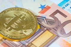 Moneta metallica del bitcoin dorato sopra le euro banconote Fotografie Stock