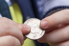 Moneta nelle mani di un bambino Fotografie Stock