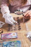 Moneta raccoglibile nella mano del ` s della donna tramite la lente d'ingrandimento Fotografie Stock Libere da Diritti
