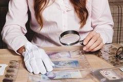 Moneta raccoglibile nella mano del ` s della donna tramite la lente d'ingrandimento Fotografia Stock
