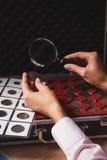 Moneta raccoglibile nella mano del ` s della donna tramite la lente d'ingrandimento Fotografia Stock Libera da Diritti