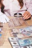 Moneta raccoglibile nella mano del ` s della donna tramite la lente d'ingrandimento Fotografie Stock