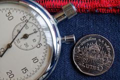 Moneta tailandese con una denominazione di 5 baht e cronometro su vecchio denim blu scuro indossato con il contesto rosso della b immagini stock