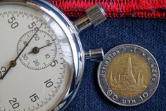 Moneta tailandese con una denominazione di 10 baht e cronometro sui vecchi jeans blu scuro portati con il contesto rosso della ba fotografia stock