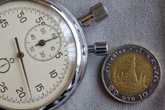 Moneta tailandese con una denominazione di 10 baht e cronometro sul contesto grigio del denim - fondo di affari fotografia stock libera da diritti