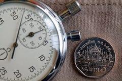 Moneta tailandese con una denominazione di 5 baht e cronometro sul vecchio contesto beige del denim - fondo di affari immagini stock