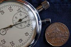 Moneta tailandese con una denominazione di 5 baht e cronometro sul vecchio contesto blu indossato del denim - fondo di affari immagini stock libere da diritti