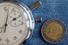 Moneta tailandese con una denominazione dieci della baht (lato posteriore) e del cronometro sul contesto blu del denim - fondo di fotografia stock
