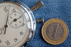 Moneta turca con una denominazione di 1 Lira e cronometro sul contesto blu consumato del denim - fondo di affari fotografie stock