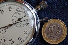 Moneta turca con una denominazione di 1 Lira e cronometro sul contesto blu indossato scuro del denim - fondo di affari immagine stock