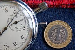 Moneta turca con una denominazione di 1 Lira e cronometro sulle blue jeans con il contesto rosso della banda - fondo di affari immagini stock