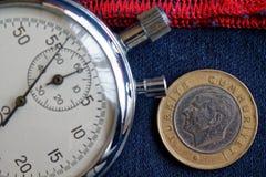 Moneta turca con una denominazione di una Lira (lato posteriore) e del cronometro su denim blu con il contesto rosso della banda  fotografie stock libere da diritti