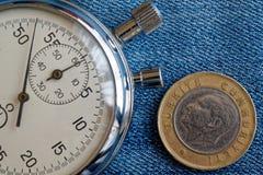 Moneta turca con una denominazione di una Lira (lato posteriore) e del cronometro sul contesto consumato delle blue jeans - fondo immagini stock libere da diritti