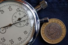 Moneta turca con una denominazione di una Lira (lato posteriore) e del cronometro sul contesto indossato scuro delle blue jeans - fotografia stock libera da diritti