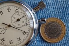 Moneta turca con una denominazione di una Lira (lato posteriore) e del cronometro sul vecchio contesto delle blue jeans - fondo d fotografia stock