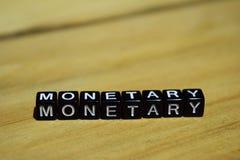 Monetair geschreven op houten blokken Inspiratie en motivatieconcepten stock foto's