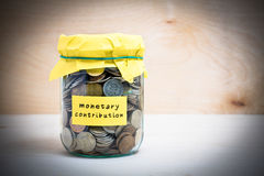 Monetary contribution. Financial concept. Coins in glass money jar with monetary contribution label. Wooden background Royalty Free Stock Images