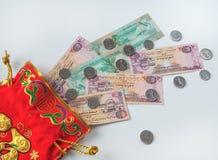 Monete arabe dei dirham Banconote arricciate in sue mani Immagini Stock