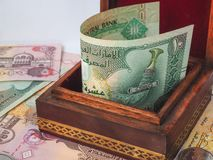 Monete arabe dei dirham Banconote arricciate in sue mani Fotografia Stock