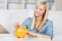 Monete cadenti sorridenti della donna nel porcellino salvadanaio Fotografia Stock Libera da Diritti
