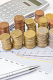 Monete, calcolatore e penna sopra il grafico Fotografie Stock Libere da Diritti