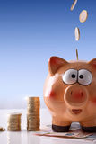 Monete che cadono sul porcellino salvadanaio con il fondo impilato del blu delle monete Immagini Stock
