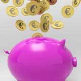 Monete che entrano in porcellino salvadanaio che mostra prestito europeo Immagini Stock Libere da Diritti
