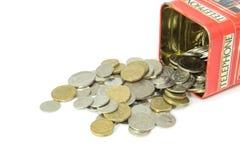 Monete che si rovesciano dal contenitore di soldi immagini stock