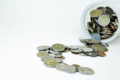 Monete che straripano un barattolo di vetro dei soldi Fotografie Stock