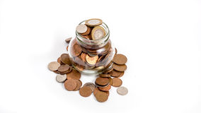 Monete che traboccano dal barattolo dei soldi Fotografia Stock