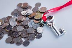 Monete con la chiave d'argento ed il nastro rosso Immagini Stock