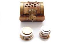 Monete contro la cassa antica verniciata di legno Fotografia Stock