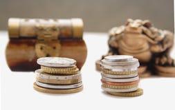 Monete contro la cassa di legno a fotografie stock