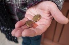 Monete degli euro a disposizione della donna povera Fotografia Stock